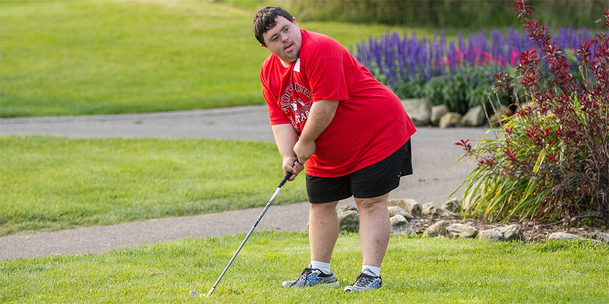 A Special Olympics Minnesota golf athlete wearing a red shirt holds his club and looks into the distance