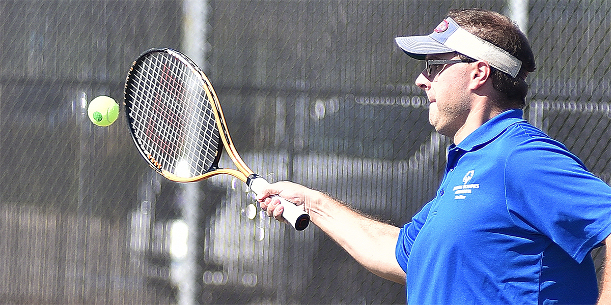 A Special Olympics Minnesota tennis athlete in a blue shirt raises his racquet to hit the ball